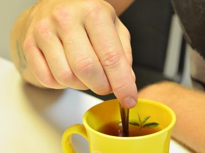 Мужчина помешивает зелёный чай